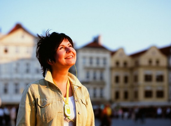 A happy tourist girl listening electronic tour guide in Prague