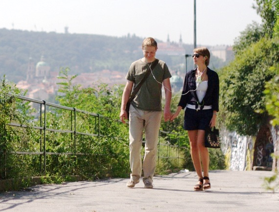 A couple of tourists walking and listening electronic tour guide in Prague